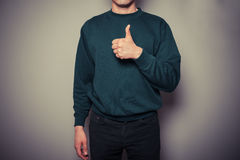 Young man giving thumbs up Stock Image