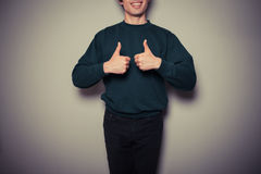 Young man giving thumbs up Stock Photography