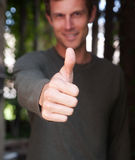 Young man giving a thumbs up hand gesture Stock Photo
