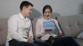 Young man giving Valentine gift box and bouquet of red roses to his girlfriend.  stock footage
