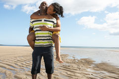 Young Man Giving Woman Piggyback Along Shoreline. Of Beach Royalty Free Stock Image