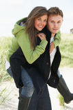Young Man Giving Woman Piggyback In Dunes Stock Photo