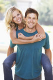 Young Man Giving Woman Piggyback Outdoors Royalty Free Stock Image