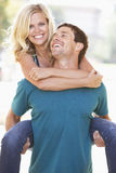 Young Man Giving Woman Piggyback Outdoors. Smiling To Camera royalty free stock photography