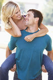 Young Man Giving Woman Piggyback Outdoors Royalty Free Stock Images