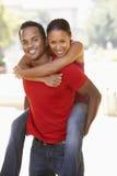 Young Man Giving Woman Piggyback Outdoors. Smiling To Camera stock photos