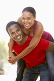 Young Man Giving Woman Piggyback Outdoors Stock Images