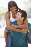 Young Man Giving Woman Piggyback Outdoors Stock Photo