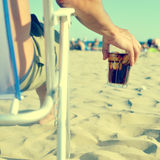 Young man with a glass with cola drink on the beach, with a filt. Young man sitting in a canvas chair holding a glass with refreshing cola drink on the beach Stock Photo