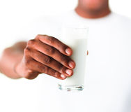 Young man with a glass of milk. On his hand Stock Image