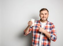 Young man with glass of tasty milk. On light background Stock Photography