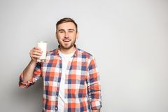 Young man with glass of tasty milk. On light background Stock Photos