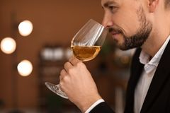 Young man with glass of wine indoors. Professional sommelier Stock Photography