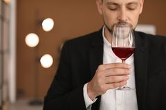 Young man with glass of wine indoors. Professional sommelier Royalty Free Stock Photo