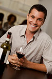 Young man with a glass of wine in a restaurant. Handsome young man with a glass of wine smiling at camera in a restaurant Royalty Free Stock Photo