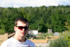 A young man in glasses. On the background of nature and tree Stock Photo