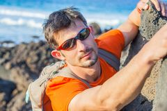 Young man in glasses with backpack climbing Royalty Free Stock Images