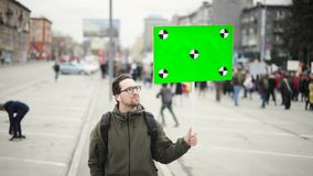 Happy young man on city demonstration holds poster with green screen in his hand.