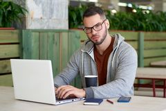 A young man with glasses and a casual hoodie is engaged in business sitting at a table in a cafe with a laptop. Stock Image