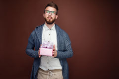 Young man in glasses and casual outfit holding small pink gift b. Ox on studio brown background Stock Image