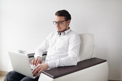 Young Man in Glasses checks mail sitting chair While Using Laptop. White Background. stock images