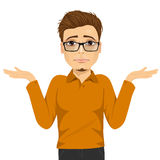 Young man with glasses in doubt making shrug expression Royalty Free Stock Image
