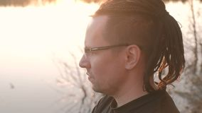 Young man in glasses with dreadlocks looking at the river, turns to face the camera and smiles. Close-up face. Young man in glasses with dreadlocks looking at stock video