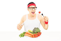 Young man with glasses eating vegetables Stock Photography