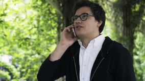 Young man in glasses enjoying a stroll in a park and a phone conversation stock video footage