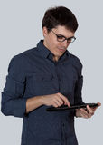 Young man in glasses enjoys tablet Stock Images