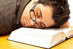 Young man with glasses fell asleep on a book royalty free stock images