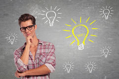 Young Man with glasses Having many Ideas. Light bulbs around him Stock Photos