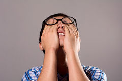 Young man glasses hiding his head in his hands Stock Images