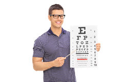 Young man with glasses holding an eyesight test Royalty Free Stock Photos
