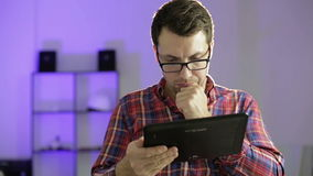 A young man in glasses holding a tablet in hands and looking for information on the Internet. stock video