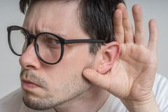 Young man with glasses is listening to you carefully stock image
