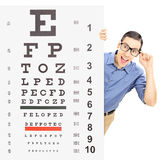 Young man with glasses peeking behind eyesight test. Isolated on white background, shot with a tilt and shift lens Stock Photography
