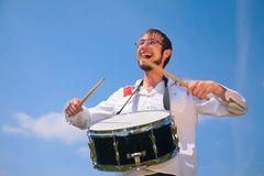 Young man in glasses plays on drum Royalty Free Stock Image