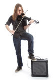Young man with glasses plays electric violin standing in studio Stock Image