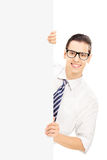 Young man with glasses posing behind a blank panel Stock Image