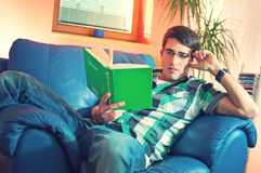 Young man with glasses reading book Royalty Free Stock Photos