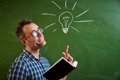 A young man with glasses is reading a book, an idea comes to mind on the background of a blackboard with a chalked light bulb stock photography