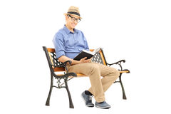 Young man with glasses reading a book on wooden bench Royalty Free Stock Photo