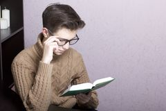 A young man with glasses reflects on an open book. Hand holding glasses for the bow. Thoughtful reading.  royalty free stock image