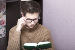 A young man with glasses reflects on an open book. Hand holding glasses for the bow. Thoughtful reading.  royalty free stock photo