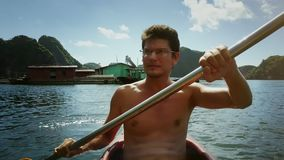 Young Man in Glasses Rows Kayak against Floating House. Young man in glasses rows kayak with yellow paddle against floating house large boat and pictorial stock video footage
