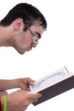 Young man with glasses seated reading a book Royalty Free Stock Photos