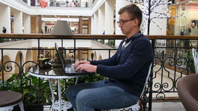 Young man in glasses are sitting at table in shopping mall and working on a laptop.  Royalty Free Stock Photo