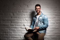 Young man in glasses sitting at wall reading book Royalty Free Stock Photo