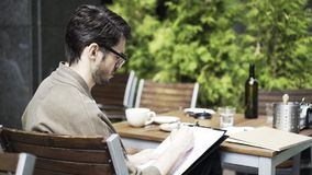 Young man in glasses sketching in a cafe outside, side view. Side view of a handsome young artist in glasses making sketches in a cafe in the street. Locked down stock footage